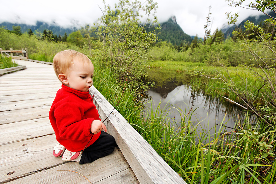 Young girl sitting on edge of wooden boardwalk trail with twigs, Big Four Ice Caves Trail, Mt Baker Snoqualmie National Forest, Washington, USA