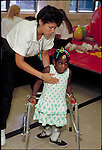 physical therapist helping young girl with cerebral palsy using walker