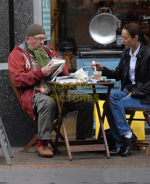 DAVID BAILEY & CATHERINE BAILEY.Enjoying a coffee outside a cafe in Oxford Street, London, England, UK,.October 31st 2009..full length sitting table hat glasses red hoodie green scarf married couple husband wife jeans drink reading book leather jacket black jeans .CAP/IA.©Ian Allis/Capital Pictures