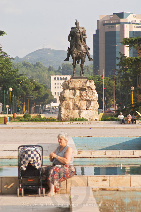 The statue of the 15th century warrior and national hero Skanderburg Skanderbeg on a huge stone base. A woman sitting on the ledge of a fountain with a baby pram. The Tirana Main Central Square, Skanderbeg Skanderburg Square. Tirana capital. Albania, Balkan, Europe.