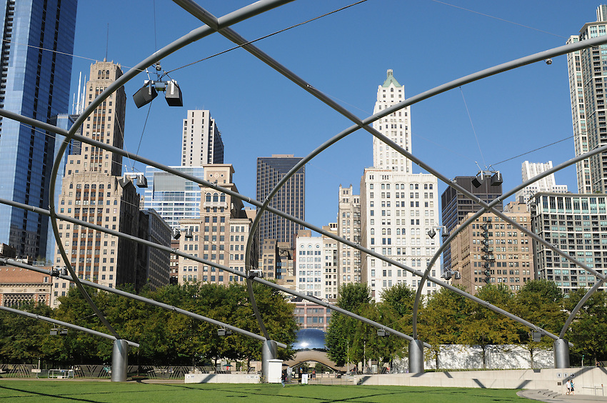 """The Chicago skyline seen through the sweeping canopy of the Jay Pritzker Pavillion, a Frank Gehry masterwork situated within magnificent Millenium Park, at center Anish Kapoor's """"Cloud Gate""""."""
