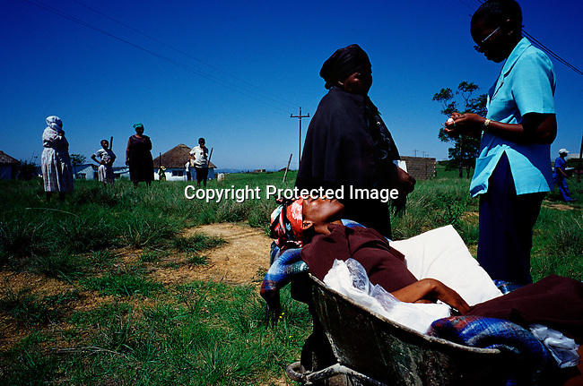 Busisiwe Mfeka, 28, is dying of Aids. She rests in a wheelbarrow, as a hospice worker drops off her and her mother in Izingolweni, a rural village in Southern Natal, South Africa. South Africa has one of the highest HIV/Aids infection rates worldwide and also the largest ARV drugs programme. (Photo by: Per-Anders Pettersson)