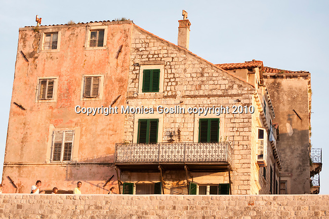 People walking on the old city wall at sunset in Dubrovnik, Croatia.