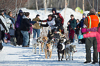 Cindy Abbott grabs a hot dog from the Horizon Lines checkpoint on the bike/ski trail during the ceremonial start of the Iditarod sled dog race Anchorage Saturday, March 2, 2013. ..Photo (C) Jeff Schultz/IditarodPhotos.com  Do not reproduce without permission