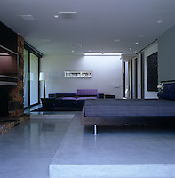 The bed in the master bedroom stands on a concrete platform with a large purple sectional sofa against one wall