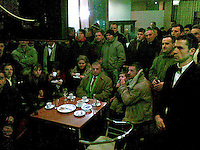 Crowds of people and a waiter inside the Grand Hotel watch television reports live from Belgrade as crowds launch attacks on Western embassies.
