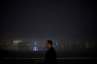 Exchange Place, United States. 11th February 2013 -- A man walks to the train station during a foggy night as the skyline of New York's Lower Manhattan and One World Trade center are seen from Exchange Place in New Jersey. Photo by Eduardo Munoz Alvarez / VIEWpress.