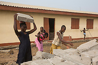 Ghana - Fuveme - Villagers carry the bricks of a house that has just been demolished by high tide, they try to save as many as possible in order to rebuild the house in a safer area further away from the sea.<br /> <br /> Nestled between the ocean and the Volta river estuary, the village of Fuvemeh has seen its territory reduced from several kilometers to few hundred meters. Nowadays, the villages sits on a narrow strip of land which separates the coastline from the adjacent lagoon. Haunted by coastal erosion, its 1,000 inhabitants have literally nowhere to move.