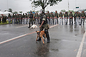 An army shock troop dog handler holds back his dog as he faces demonstrators - indigenous people, the Landless People's Movement (MST) and other civil society groups - in front of the Riocentro United Nations conference. The demonstrators are kept out of earshot and invisible to the UN conference. The United Nations Conference on Sustainable Development (Rio+20), Rio de Janeiro, Brazil, 20th June 2012. Photo © Sue Cunningham.