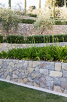 Raised terraces in the garden, where natural stone in muted colours emphasises the greenery of the planting.
