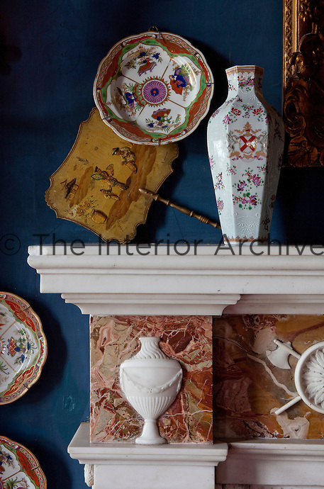 Chinese ceramics are displayed on the walls and neo-classical marble chimneypiece in the library