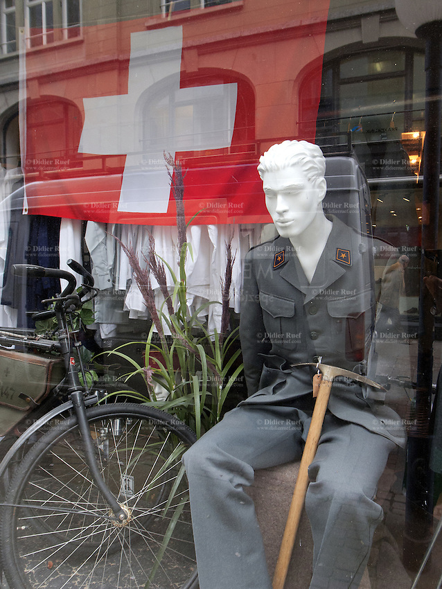 Switzerland. Canton Zürich. Zuerich. A shop sells military outfitts. A swiss flag, a military bike and a dummy model wearing a military uniform. The flag of Switzerland consists of a red flag with a white cross (a bold, equilateral cross) in the centre. It is a sovereign-state flag. 7.11.12  © 2012 Didier Ruef