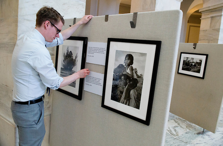"UNITED STATES - MARCH 31: Josh Hunter of MAG (Mines Advisory Group) hangs a photo exhibit in Russell Building titled ""Surviving the Peace,"" which focuses on how land mines, mortars, and munitions are still effecting survivors of formally war torn areas. (Photo By Tom Williams/CQ Roll Call)"