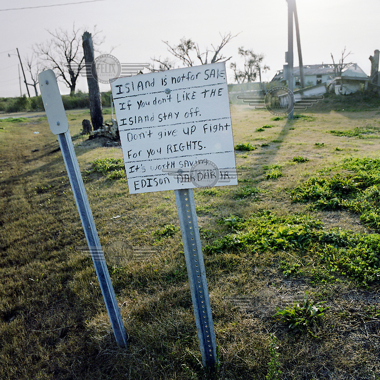 A sign at the entrance to the predominantly Native American community of Isle Jean Charles, Louisiana reflects one resident's anxiety about the potential loss of Native American land. The island's chief, Albert Naquin has been suggesting relocation plans but has been unable to find funding to move the island's inhabitants to housing on shared land further inland.