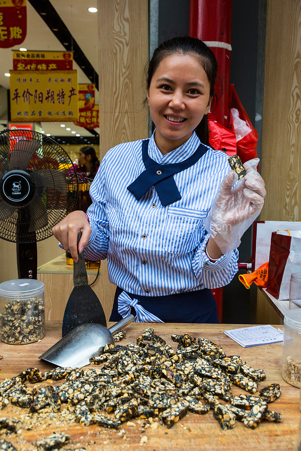 Yangshuo, China.  Preparing Peanut-brittle Candy for Bagging for sale.