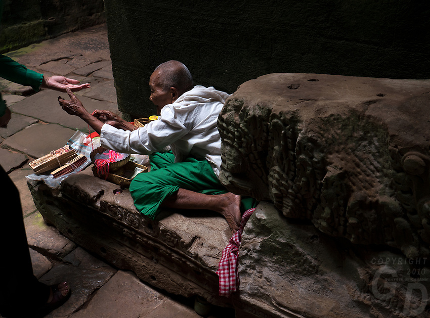 Buddhist Nun offering a visitor a religious prayer band, in the corridors of Preah Khan, Angkor, Siem Reap, Cambodia