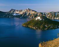 USA, Oregon, Crater Lake National Park, Sunrise on Crater Lake and Wizard Island with Garfield Peak  rising above Crater Lake; from Merriam Point.