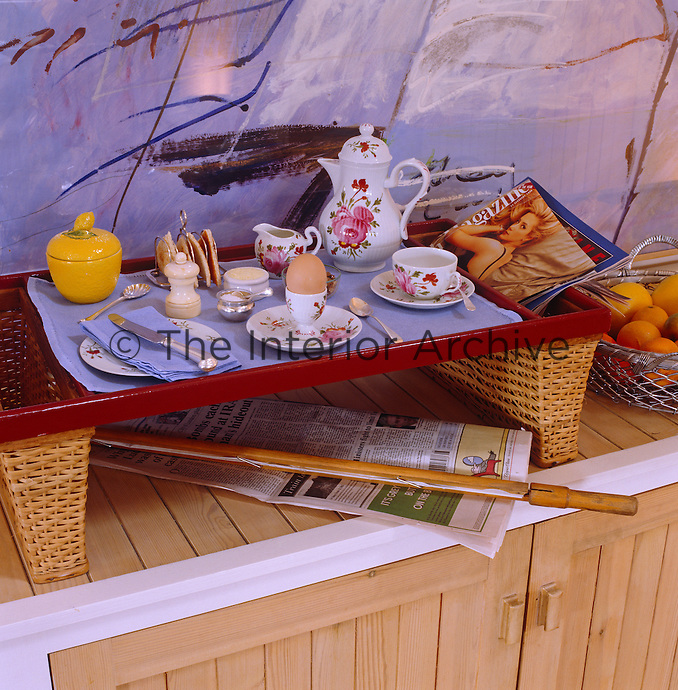 Detail of a wicker tray laid with a tempting breakfast with special baskets either side for papers and magazines