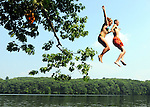 Brittany Hunt ,17,  and Dana Ferrari, 20, both of Windsor Lock, hold hands as they jump high from a tree into the Farmington River at the  Rainbow Road boat launch in Windsor, Wednesday, July 7, 2010, as temperatures made it up to 100 degrees as a heat wave continues to grip the east coast.