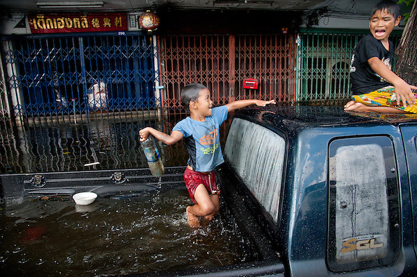 Children play in floodwater in western Bangkok, despite widespread reports that it contains diseases and dangerous animals.<br />