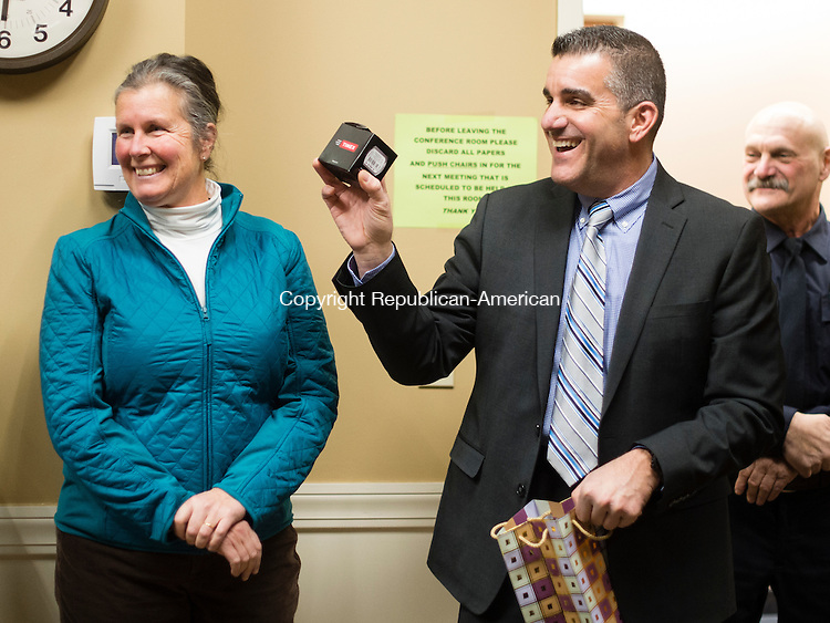 MIDDLEBURY, CT- 11 January 2015-011116EC03-    Middlebury's police chief, James Viadero, is leaving for a chief's job in Newtown. He holds up a watch the Chairman of the Police Commission gave him during a ceremony Monday night at Middlebury Town Hall. On the left is Elaine Strobel, who serves on the board of selectmen. Erin Covey Republican-American