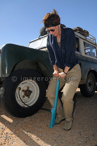 Africa, Tunisia, nr. Ksar Rhilane. Desert traveller Doris inflating a tyre with a hand compressor on a historic 1962 Land Rover. --- No releases available, but releases may not be needed for certain uses. Automotive trademarks are the property of the trademark holder, authorization may be needed for some uses.  --- Info: Image belongs to a series of photographs taken on a journey to southern Tunisia in North Africa in October 2010. The trip was undertaken by 10 people driving 5 historic Series Land Rover vehicles from the 1960's and 1970's. Most of the journey's time was spent in the Sahara desert, especially in the area around Douz, Tembaine, Ksar Ghilane on the eastern edge of the Grand Erg Oriental.