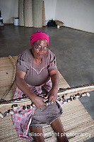 Africa, Swaziland, Malkerns.Nest organization artisan project, partnering with Gone Rural & local artisans to help market their products to global markets and better sustain their local community. Emmah Manana, works as artisan at Rosecraft, is also leaning how to use a camera to shoot her products. She's working the homemade loom (made with strings & old batteries) with her mother, Linah (pink hat), at home in their 8 corner house. Emmah learned the art of weaving from her mother who makes these grass mats used for sleeping and to wrap the dead in.