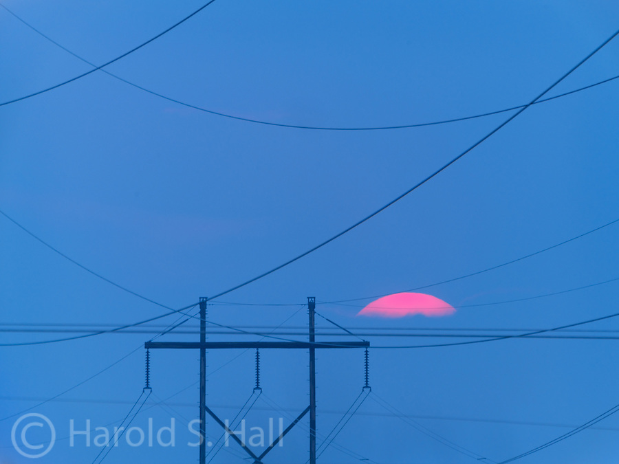 Smoke filled skies from fires in Oregon make the sun appear bright orange as the sun sets with an electrical substation as a foreground.