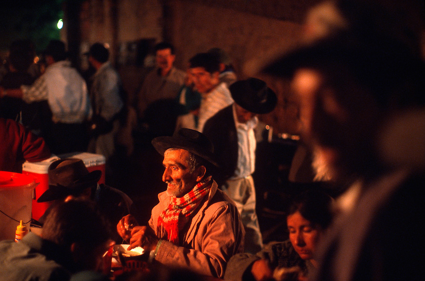 """Campesinos eat dinner at small food stands in the local produce market in Vallegrande, Bolivia Sunday, Nov. 14, 2004. Ernesto """"Che"""" Guevara was captured by the Bolivian army in 1967 in a nearby valley and executed in La Higuera days later. His body was put on public display in the laundry room of the Vallegrande hospital, then secretly buried under the air strip for 30 years. Guevara and fellow communist guerillas were attempting to launch a continent-wide revolution modeled on Guevara's success in Cuba in the late 1950s. The Bolivian government recently began promoting the area where he fought, was captured, killed and burried for 30 years as the """"Ruta del Che,"""" or Che's Route. (Kevin Moloney for the New York Times)"""