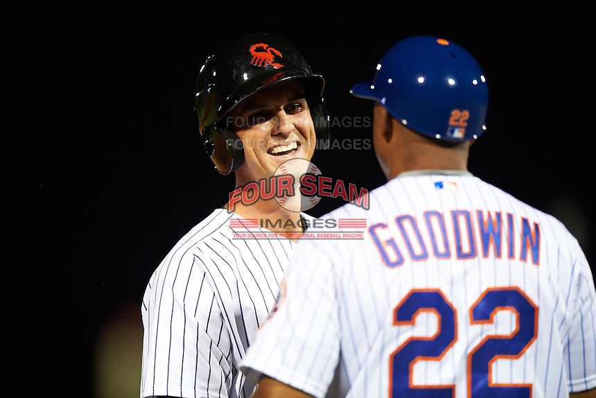 Scottsdale Scorpions Greg Bird (33), of the New York Yankees organization, smiles while talking with manager Tom Goodwin (22) during a game against the Salt River Rafters on October 20, 2016 at Scottsdale Stadium in Scottsdale, Arizona.  Scottsdale defeated Salt River 4-1.  (Mike Janes/Four Seam Images)