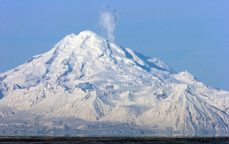 Mount Redoubt volcano vents steam during a period of volcanic unrest. The mountain is prominent on the horizon in Kenai, Alaska, 50 miles across Cook Inlet to the west.