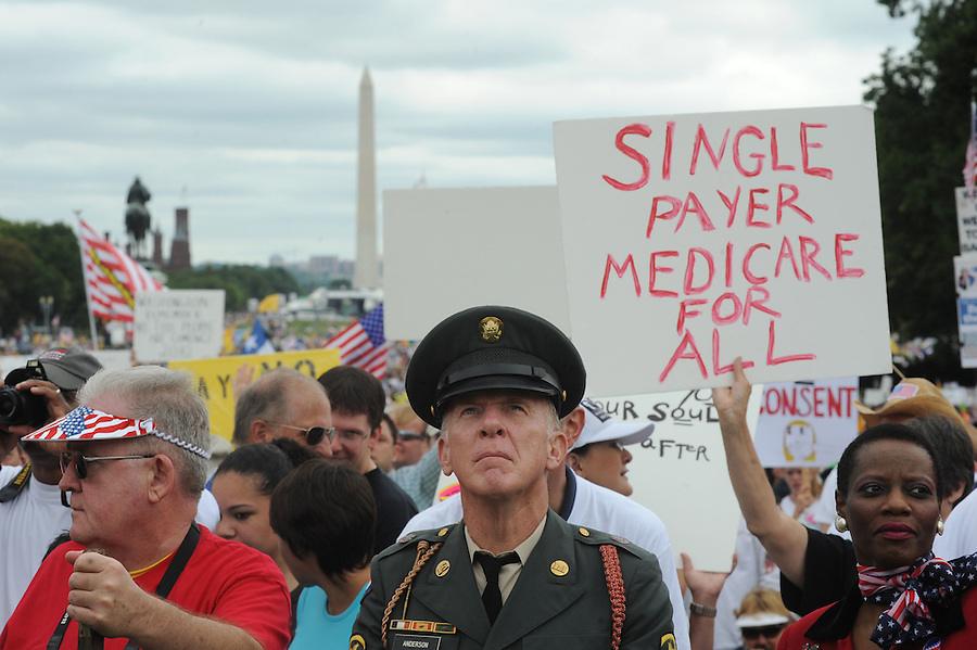 """(center) Steve Anderson, 61, of Sidney, NY, and (right) Sakina Mengle, of Rockville, MD., look toward the U.S. Capitol during the Tea Party Protest on Sept. 12, 2009 in Washington, DC. Anderson was a Combat Engineer in Vietnam. He said, """"I have a 60 ft. flag that I don't fly in defiance of the most unpatriotic, un-American president we ever had in the history of this nation."""""""