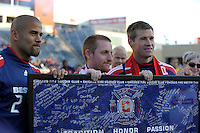 Chicago Fire forward Brian McBride (20) receives a signed poster from teammate CJ Brown and a Section 8 supporter after playing his last home game for the Chicago Fire.  The Chicago Fire tied DC United 0-0 at Toyota Park in Bridgeview, IL on Oct. 16, 2010.