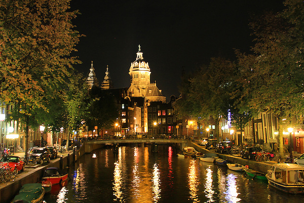 Church and canal at night, with boats, Amsterdam, Netherlands