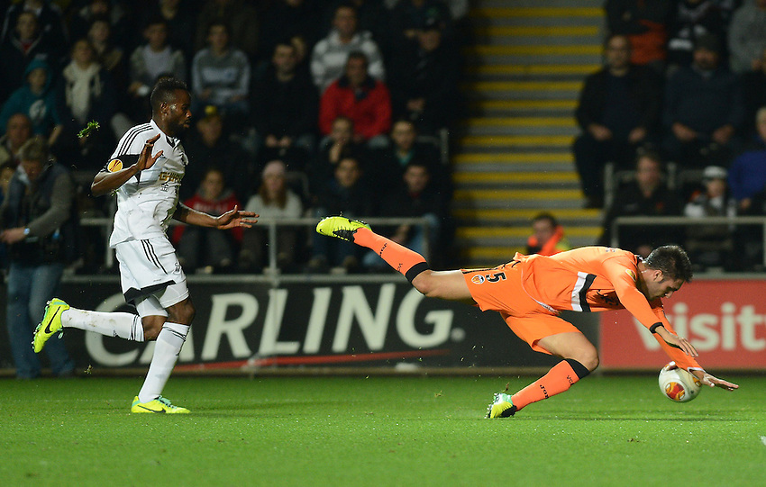 Valencia's Victor Ruiz goes down after being pushed by Swansea City's Roland Lamah <br /> <br /> Photo by Ian Cook/CameraSport<br /> <br /> Football - UEFA Europa League Group A - Swansea City v Valencia - Thursday 28th November 2013 - The Liberty Stadium - Swansea<br /> <br /> &copy; CameraSport - 43 Linden Ave. Countesthorpe. Leicester. England. LE8 5PG - Tel: +44 (0) 116 277 4147 - admin@camerasport.com - www.camerasport.com