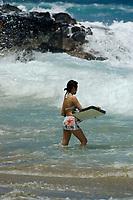 Japanese tourist bodyboarder during large surf at Magic sands beach Kailua Kona The Big Island of Hawaii