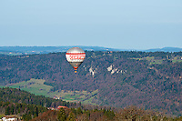 Hot air balloon flying low over the Jura mountains