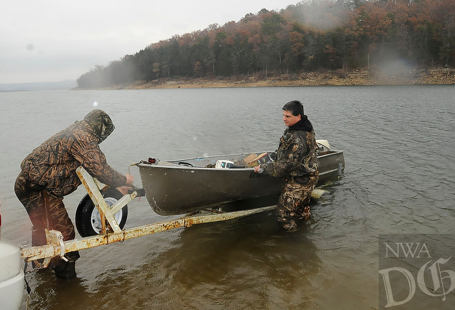 NWA Media/FLIP PUTTHOFF <br /> RAINY-DAY DUCKS<br /> Kyson Larsen, left, and his dad, Ryan Larsen load their boat on a trailer on Saturday Nov. 22 2014 after a morning duck hunt at Beaver Lake. The two were part of a five-hunter party on the lake for opening day of duck hunting season. The hunters bagged two ducks.