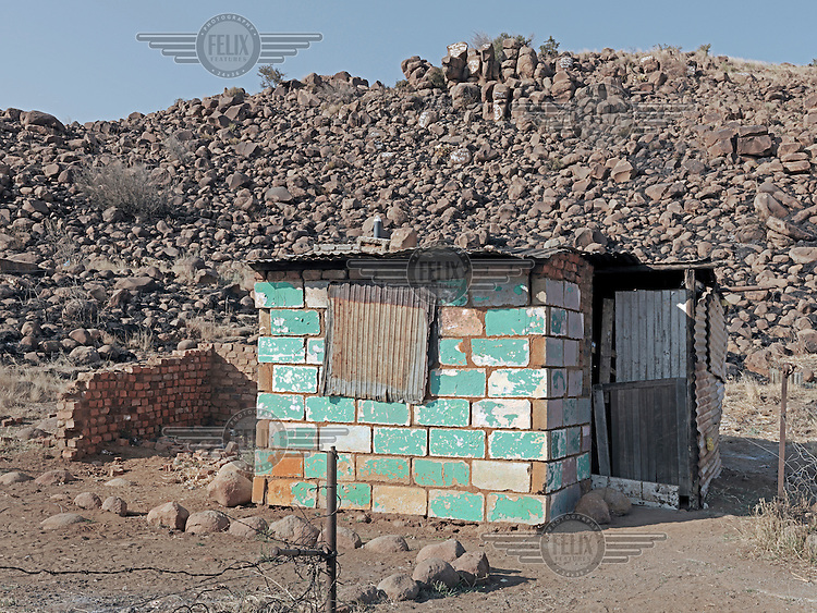 A tiny breeze block shed.  Graeme Williams' pictures of the environments occupied by some of South Africa's poorest people focus on the interiors and exteriors of people's homes, accentuating the minutiae of the occupants' day-to-day dwelling places. The bright colours captured in these photographs are suggestive of resilience, hope and a sense of humanity that survives in these poverty-stricken communities...