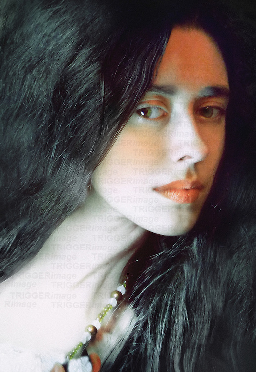 A portrait of a young woman with long black hair with a pale complexion wearing a necklace
