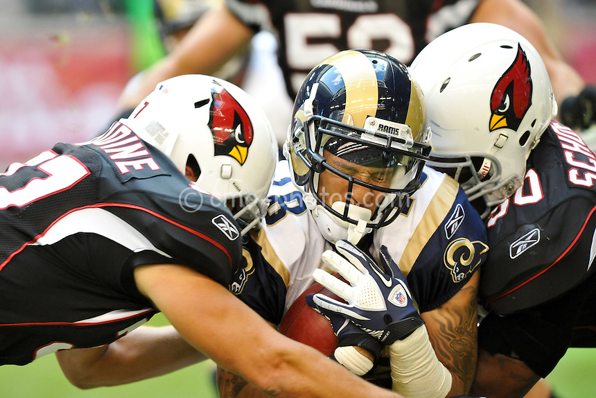 Nov 5, 2011; Glendale, AZ, USA; St. Louis Rams wide receiver Austin Pettis (18) gets tackled by Arizona Cardinals safety Sean Considine and linebacker O'Brien Schofield (50) while returning a punt in the second quarter of a game at University of Phoenix Stadium.