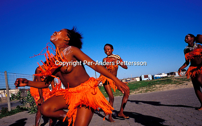 dicuxho00009. Culture Xhosa. Unidentified girls dancing traditional Xhosa dances in the school yard on August 22, 2001 in Site B Khayelitsha, a township about 35 kilometers outside Cape Town, South Africa. They are part of Siyazama aftercare center for abused children in their school. Many children are abused sexually or physically in their homes and neighborhood. Khayelitsha is one of the poorest and fastest growing townships in South Africa. People usually come from the rural areas in Eastern Cape province to find work as maids and laborers. Most people don't find work and the unemployment rate is very high, together with lot of violence and a growing HIV-Aids epidemic itÕs a harsh area to live in..©Per-Anders Pettersson/ iAfrika Photos.