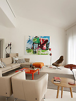 A contemporary living room in neutral tones. A Suita sofa and armchairs designed by Antonio Citterio for Vitra, form a quiet seating area within the open plan room. A bold orange coffee table and a vibrant painting by Franzisca Maderthaner brings colour to the otherwise neutral room.