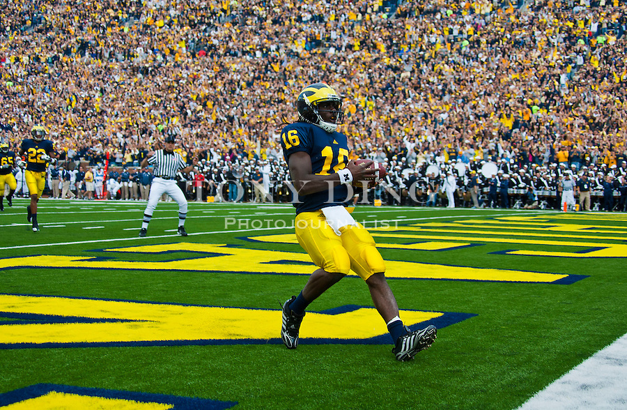 Michigan quarterback Denard Robinson (16) scores a touchdown in the first quarter of an NCAA college football game with Connecticut, Saturday, Sept. 4, 2010, in Ann Arbor, Mich. (AP Photo/Tony Ding)