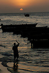 A Zanzibar resident tends to fishing boats as the tide rises in the beach adjacent to Stone Town, Zanzibar. (Rick D'Elia)<br />