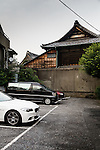 Tokyo, June 25 2013 -  Cars parked in front of a bouddhist temple in the Nezu area.