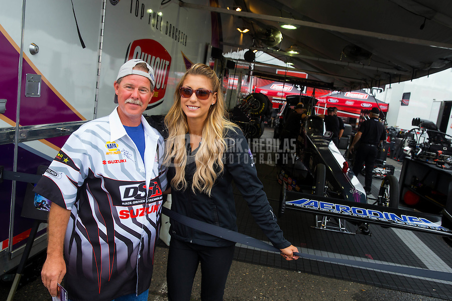 Jun 6, 2015; Englishtown, NJ, USA; NHRA top fuel driver Leah Pritchett poses with a fan during qualifying for the Summernationals at Old Bridge Township Raceway Park. Mandatory Credit: Mark J. Rebilas-