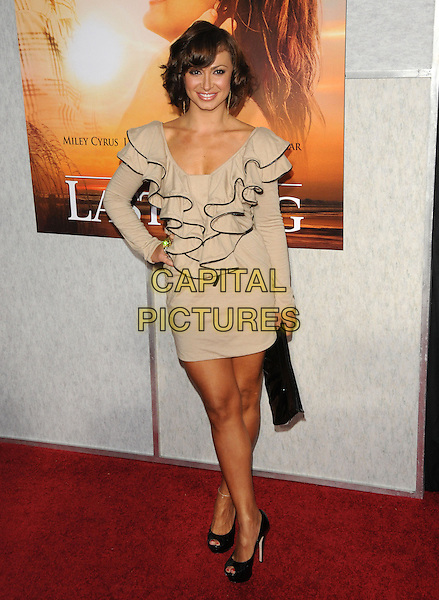 "KARINA SMIRNOFF .at the Touchstone Pictures' World Premiere of ""The Last Song"" held at The Arclight  in Hollywood, California, USA, March 25th 2010.           .arrivals full length beige ruffles ruffle neck dress long sleeved sleeve hand on hip black trim clutch bag peep toe shoes platform heels                        .CAP/RKE/DVS.©DVS/RockinExposures/Capital Pictures"