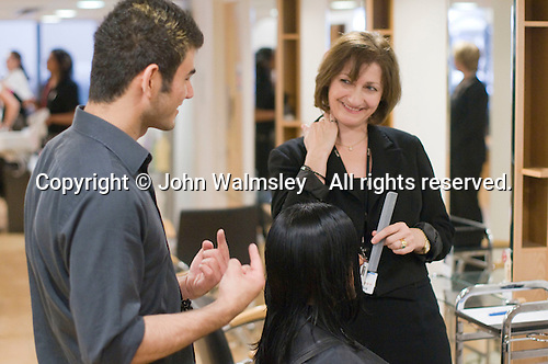 Instructor chatting happily with a student in the Arena Salon, Hair & Beauty Dept., Kingston College.