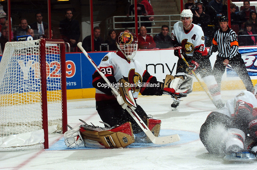 Ottawa Senators' goaltender Dominik Hasek of the Czech Republic makes a save during a game against the Carolina Hurricanes Tuesday, Nov. 22, 2005 in Raleigh, NC. Teammate Wade Redden (6) looks on from behind. Ottawa won 5-3.